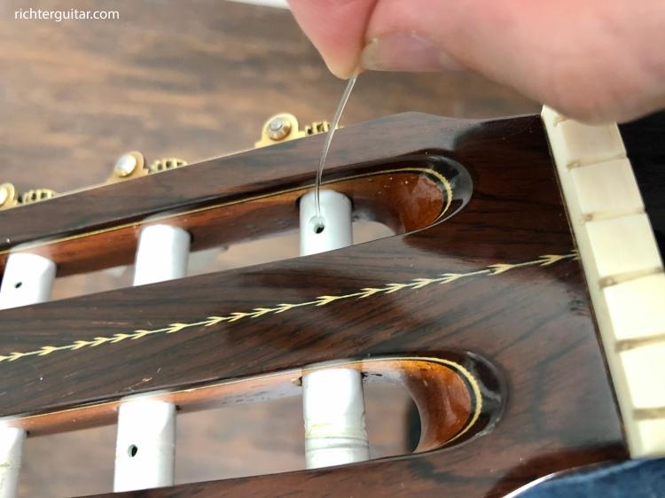Classical guitar tuning peg feeding nylon string through