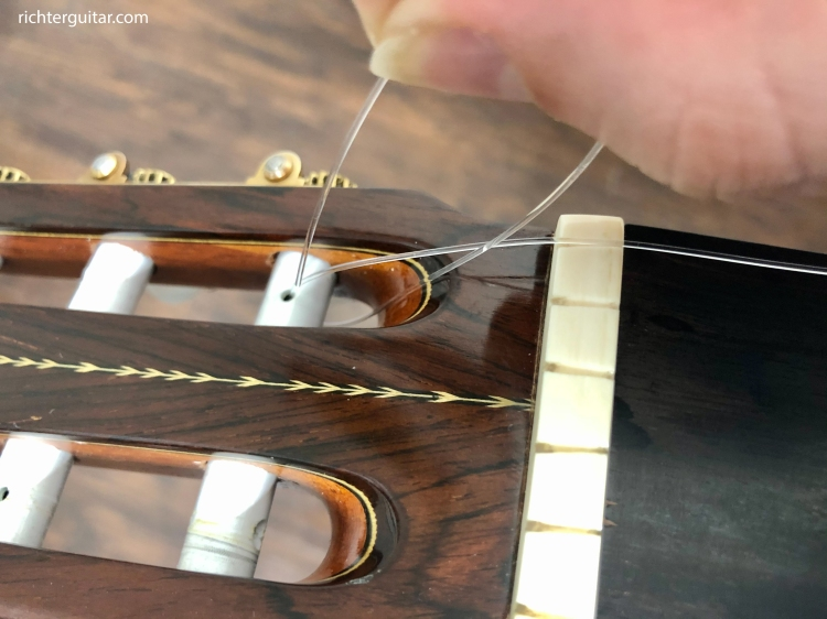 Feed the classical guitar string through the tuning peg a second time to secure it