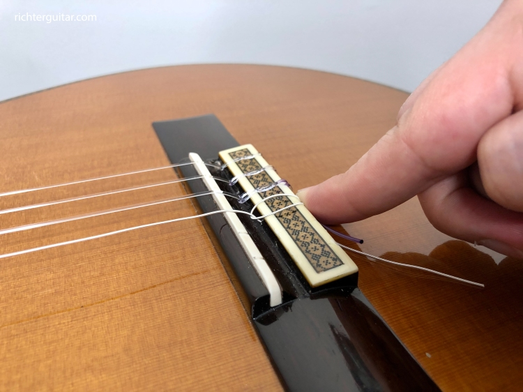 Use your finger to hold the classical guitar string tail while tuning so it