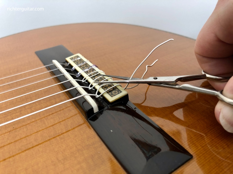 Trimming classical guitar string tail with scissors